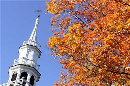 The steeple of The First Congregational Church is juxtaposed with fall colors in Sharon, Connecticut October 13, 2004. He doesn't speak Spanish and has no idea what America should do about illegal immigration, but Rev. Larry Kreps knows he's now on a list somewhere of people willing to help illegal immigrants in a time of crisis. REUTERS/Jessica Rinaldi.