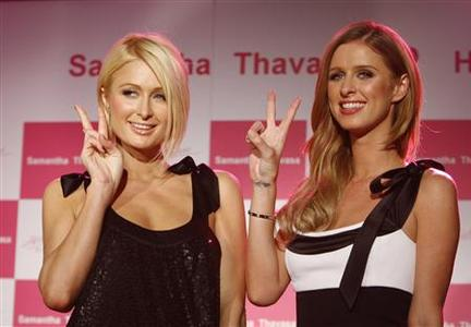 Paris Hilton (L) and her sister Nicky pose at a promotional event for Japan's fashion brand Samantha Thavasa's handbags and accessories in Tokyo in this November 5, 2007 file photo. The Hilton sisters' potential inheritance dramatically diminished after their grandfather Barron Hilton announced plans on December 26, 2007 to donate 97 percent of his $2.3 billion fortune to charity. REUTERS/Kim Kyung-Hoon/Files
