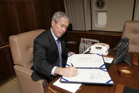 President George W. Bush signs into law H.R. 2764 during a flight aboard Air Force One on December 26, 2007. REUTERS/Chris Greenberg/Handout