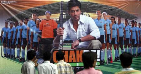People stand in front of a movie poster of ''Chak De! India'' outside a movie hall in Mumbai in this August 14, 2007 file photo. The magic recipe that helped ''Chak De! India'' score at the Bollywood box-office comprised women's hockey, a dash of patriotism -- and its Muslim protagonist. REUTERS/Punit Paranjpe