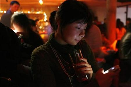A Chinese woman checks her cellular phone during an event organized by a dating Web site, in a club in Shanghai, January 20, 2007. Online dating renews women's hope in love and sex, but can be just as disappointing as the real-life dating scene, according to new Canadian research. REUTERS/Nir Elias