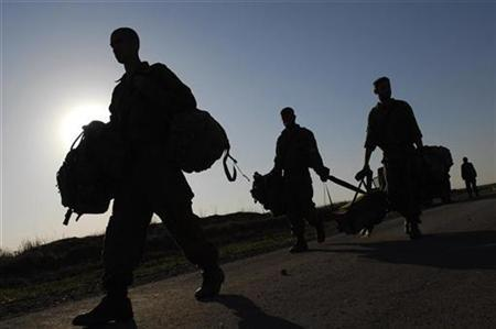 Israeli soldiers carry equipment near Kibbutz Ein Hashlosha after operating in the Gaza Strip December 27, 2007. Israel said on Saturday it had recently seized a truck carrying chemicals used to make explosives hidden in bags marked as EU aid for the Hamas-controlled Gaza Strip. REUTERS/Amir Cohen