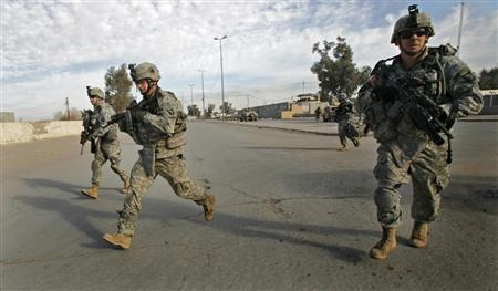 U.S. Army soldiers with the 101st Airborne Division run across a street during a patrol in Baiji December 28, 2007. U.S. and Iraqi commanders said on Saturday there had been a remarkable improvement in the country's security over the past year, but the top American general also warned that the gains could be reversed. REUTERS/Bob Strong
