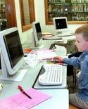 <p>Un jeune Américain dans une bibliothèque de Watertown , dans le Dakota du Sud. Plus de la moitié des Américains disent s'être rendus dans une bibliothèque l'an dernier, la plupart pour l'accès internet qu'elles proposent plus que pour les livres, selon une étude du Pew Internet & American Life Project. /Photon d'archives/REUTERS/Jeff Christensen</p>