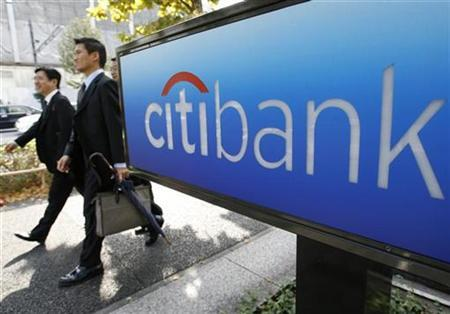 Men walk past a Citibank sign outside its Tokyo branch, November 5, 2007. Citigroup Inc, the largest U.S. bank, may need to write down $12 billion of debt and boost reserves for bad loans by $1 billion as the global credit crunch deepens, a Sanford C. Bernstein & Co analyst said. REUTERS/Toru Hanai