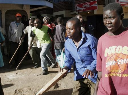 Opposition supporters run armed with sticks during ethnic violence in Nairobi January 2, 2008. President Mwai Kibaki's government accused rival Raila Odinga's party of unleashing ''genocide'' in Kenya on Wednesday as the death toll from tribal violence over a disputed election passed 300. REUTERS/Thomas Mukoya