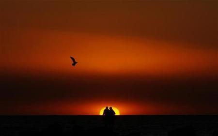 A couple watches the sunset on Venice Beach in Los Angeles December 26, 2007. Four out of 10 Americans say they don't need a marriage certificate to prove love or commitment, according to a new online survey. REUTERS/Lucy Nicholson