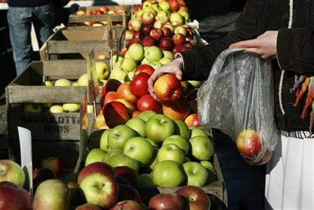 A shopper looks at apples at a farmers market in New York March 11, 2007. People who drink moderately, exercise, quit smoking and eat five servings of fruit and vegetables each day live on average 14 years longer than people who adopt none of these behaviours, researchers said on Tuesday. REUTERS/Lucas Jackson