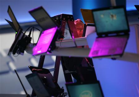 A worker sets up a display of laptop computers at the Intel booth as exhibitors prepare for the Consumer Electronics Show (CES) in Las Vegas, January 6, 2008. REUTERS/Steve Marcus