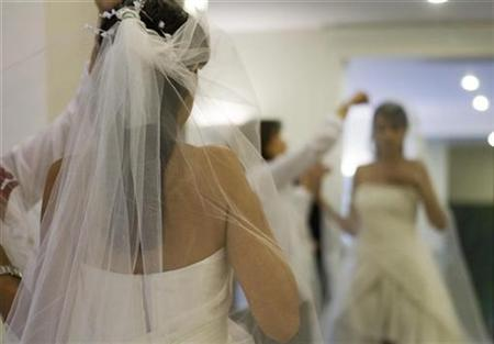 A dress designer checks the fit of a veil on a bride at a high fashion studio in north Tehranm, Iran, October 2, 2007. Traditional white wedding gowns aren't making it to the altar this year as Canadian brides-to-be commit, instead, to color. REUTERS/Caren Firouz
