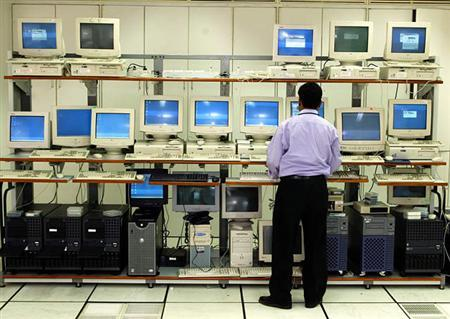 A man looks at an array of computers in a file photo. REUTERS/Pawel Kopczynski