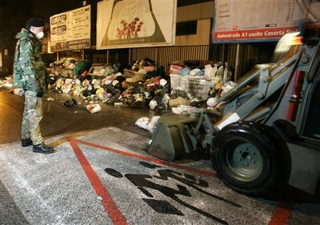 Italian soldiers remove garbage from a road outside a school in Caserta near Naples January 7, 2008. REUTERS/Agnfoto