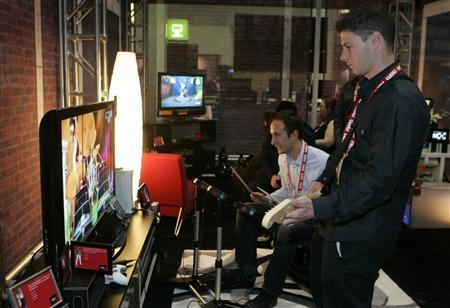 Lucas Charbit (C) and Thomas Latina, both of France, play Rock Band on a Xbox 360 console at the AMD ''Innovation Experience'' during the Consumer Electronics Show (CES) in Las Vegas, Nevada January 7, 2008. REUTERS/Steve Marcus