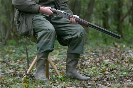 A hunter holds his shotgun during a shoot in a forest at Bayenghem-les-Seninghem, near Saint-Omer, France, November 3, 2006. A Houston-area man was killed in a hunting accident after his dog stepped on a loaded shotgun in the back of a pick-up truck, triggering a blast that pierced the vehicle and the hunter's leg, a local sheriff said. REUTERS/Charles Platiau