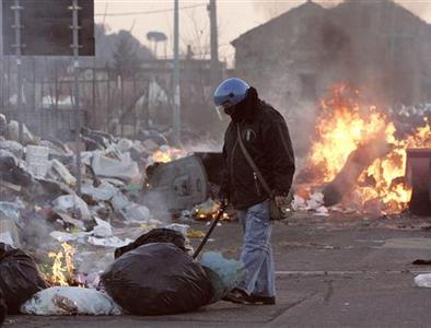 A police officer wearing a riot helmet inspects garbage burning on a street in Naples January 8, 2008. REUTERS/Salvatore Esposito/Agnfoto