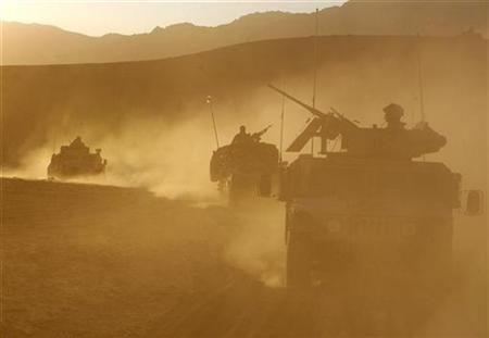 U.S and Dutch soldiers drive along a dusty road in a village in Baluchi pass in Uruzgan province, Afghanistan November 1, 2007. REUTERS/Goran Tomasevic