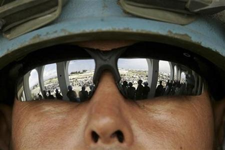 A U.N. peacekeeper keeps a lookout while Haitians take part in a peaceful rally calling for peace in the volatile neighborhood of Cite-Soleil in Port-au-Prince April 27, 2007. REUTERS/Eduardo Munoz
