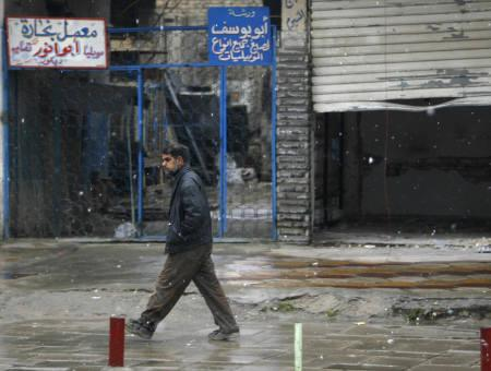 A resident walks along a street during snowfall in Baghdad January 11, 2008. Snow fell on Baghdad on Friday for the first time in memory, and delighted residents declared it an omen of peace. REUTERS/Mahmoud Raouf Mahmoud