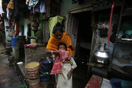 A rehabilitated sex worker cleans her son in front of her one room house in the red light district of Kalighat in Kolkata January 4, 2008. Authorities in eastern India have teamed up with prostitutes as the officials accelerate a drive against the trafficking of girls into the trade. REUTERS/Parth Sanyal