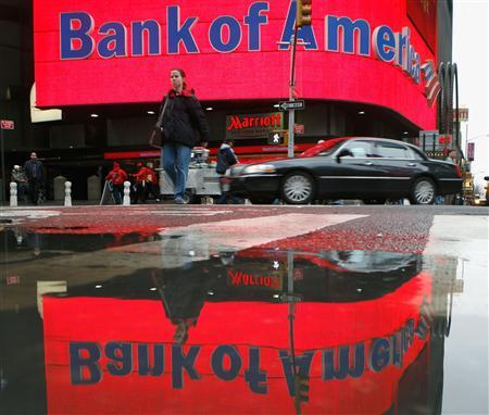 A woman is reflected in a puddle as she passes a Bank of America branch in New York's Times Square January 11, 2008. REUTERS/Brendan McDermid
