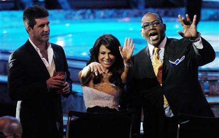 ''American Idol'' judges Simon Cowell (L), Paula Abdul (C) and Randy Jackson wave to the crowd during the show's finale at the Kodak Theater in Hollywood, May 24, 2006. ''American Idol'' is poised to set ratings records when Fox's talent show returns to the airwaves with a four-hour season premiere on Tuesday and Wednesday. REUTERS/Chris Pizzello