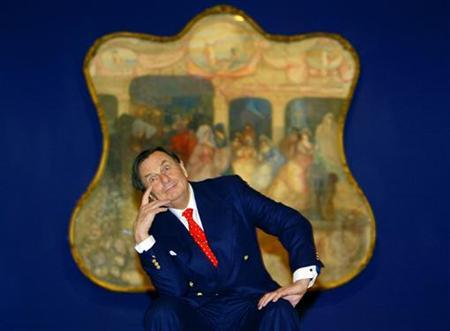 Australian comedian Barry Humphries poses in front of one of Australian artist Charles Condor's paintings at the launch of his retrospective at the New South Wales Art Gallery in Sydney June 12, 2003. Humphries has been ordered to rest for six months because of complications over appendix surgery, a spokesman for the Magners Glasgow International Comedy Festival said on Sunday. REUTERS/David Gray