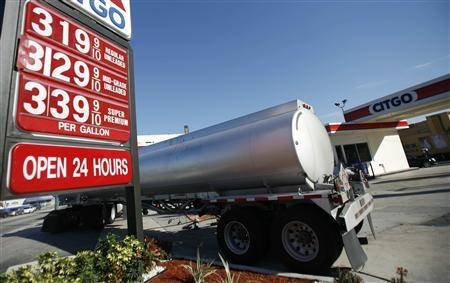 A sign displays prices at a gas station as the underground storage tank of a gas station gets fuelled up in Miami, Florida January 2, 2008. REUTERS/Carlos Barria