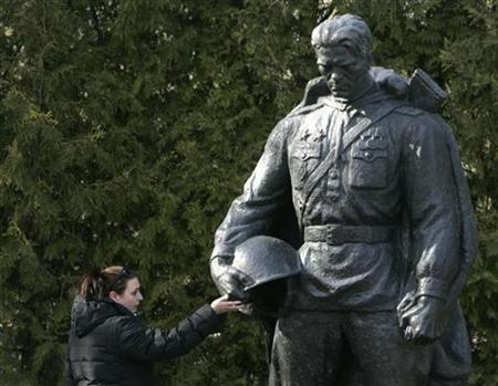 A woman touches a bronze statue of a World War Two Red Army soldier that was relocated from the city centre to a military cemetery in Tallinn April 30, 2007. Estonia put four ethnic Russians on trial on Monday over riots last year when the authorities moved the Soviet-era war memorial, protests which the authorities say were in part organized and financed from Russia. REUTERS/Ints Kalnins