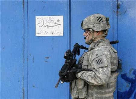 A U.S. soldier stands guard near a shop which is closed during a patrol in Baghdad's Adhamiya district January 5, 2008. REUTERS/Mahmoud Raouf Mahmoud