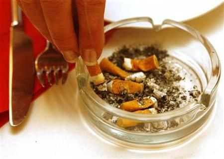 A woman puts out a cigarette in a restaurant in Munich, December 31, 2007. A Hamburg newspaper that reported last week on a computer company manager who said he fired three non-smokers because they had threatened disruptions after asking for a smoke-free environment said on Monday the story was a hoax. REUTERS/Alexandra Beier