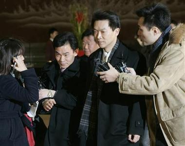 Agents (2nd and 3rd L) from a special team of South Korean prosecutors investigating Samsung Group refuse reporters' questions as they walk out of the lobby of the group headquarters in Seoul, January 15, 2008. REUTERS/Han Jae-Ho
