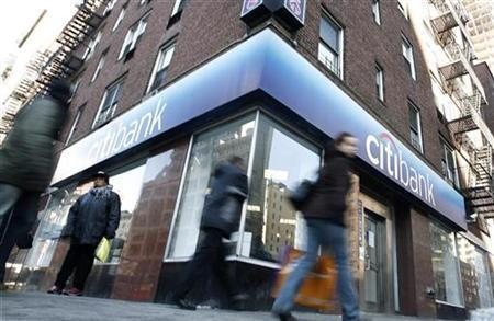 People walk past a Citibank branch in New York, February 17, 2007. Citigroup wrote off a colossal $18.1 billion on Tuesday and secured new capital as Merrill Lynch, also seen heading for big losses due to the U.S. subprime mortgage meltdown, announced a $6.6 billion shot in the arm. REUTERS/Keith Bedford