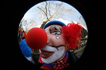 A carnival reveller dressed as a clown celebrates on the street in Berlin February 18, 2007. REUTERS/Pawel Kopczynski