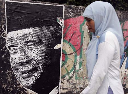 A woman walks past a poster of former Indonesian President Suharto in Jakarta, December 17, 2008. REUTERS/Dadang Tri