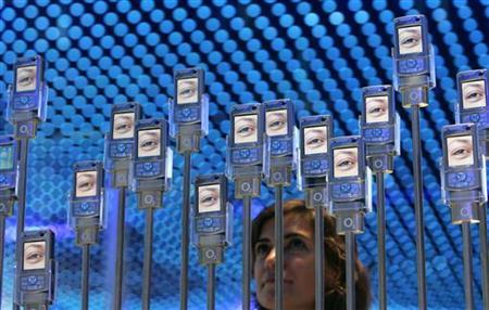 A woman poses next to cell phones at the 'Internationale Funkausstellung' (IFA) 2006 consumer electronics fair in Berlin September 1, 2006. Virtual worlds, mobile coupons and bar-code readers on cell phones are the next technology wave that U.S. chain stores must ride if they hope to stay competitive in the fast-changing world of global retail. . REUTERS/Tobias Schwarz
