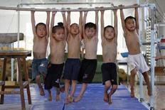 <p>Мальчики висят на перекладине во время тренировки в Шанхае 7 августа 2007 года. Международный олимпийский комитет назвал Москву и Сингапур финальными претендентами на проведение Юношеских олимпийских игр в 2010 году, сообщило правительство азиатского государства в понедельник. (REUTERS/Nir Elias)</p>
