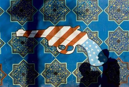 Men walk past a mural on a wall of the former U.S. embassy in central Tehran, January 14, 2008. REUTERS/Morteza Nikoubazl