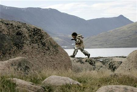 An Inuit girl dressed in traditional clothing plays on rocks in Pangnirtung, Nunavut July 5, 2007. The Inuit in Canada's far north have lifespans 12 to 15 years shorter than the average Canadian's, government data showed on Wednesday, putting the aboriginal people on a par with developing countries such as Guatemala and Mongolia. REUTERS/Chris Wattie