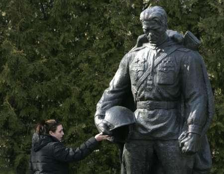 A woman touches a bronze statue of a World War Two Red Army soldier that was relocated from the city centre to a military cemetery in Tallinn April 30, 2007. An Estonian court has fined a man in the only conviction linked to cyber attacks on official Web sites during last year's riots over the relocation of the Soviet-era war memorial, it said on Thursday. REUTERS/Ints Kalnins