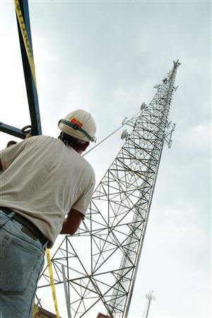 A worker looks at a cellular tower in a publicity photo. REUTERS/PRNewsFoto