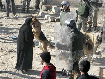 A Palestinian woman stands among Egyptian riot police as she tries to cross into Egypt through the destroyed section of the border wall between the Gaza Strip and Egypt, January 25, 2008. REUTERS/Suhaib Salem