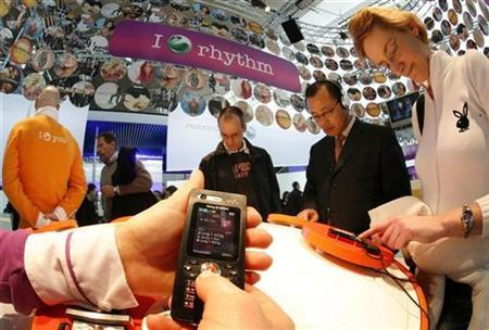 A model displays a new W880i Walkman phone by Sony Ericsson during first public day at the CeBIT computer fair in Hanover March 15, 2007. REUTERS/Christian Charisius