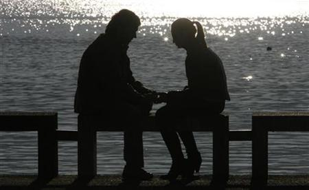 A couple is silhouetted in this March 13, 2007 photo. Lovelorn staff at a Japanese marketing company can take paid time off after a bad break-up with a partner, with more ''heartache leave'' on offer as they get older. REUTERS/Christian Hartmann