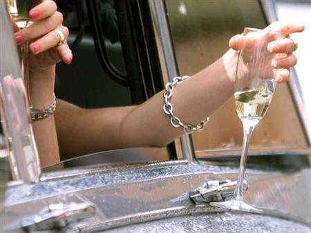 A woman holds a glass of champagne out of a car window in an undated file photo. Moderately happy people are wealthier -- and maybe healthier -- than extremely happy individuals, according to a psychologist who has researched happiness for more than two decades and his associates. REUTERS/Ian Waldie