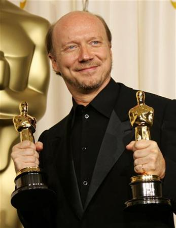 Producer Paul Haggis poses with his Oscars for best picture and best original screenplay for his work on ''Crash'' at the 78th annual Academy Awards in Hollywood, March 5, 2006. ''Crash,'' the racially charged drama that won the Oscar for best picture of 2005, is coming to the small screen later this year as a TV series for the Starz network, the pay cable channel said on Monday. REUTERS/Mike Blake