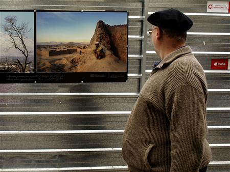 A passer-by looks at photographs during an exhibition of press photography, in Vitoria, Spain October 18, 2007. REUTERS/Vincent West