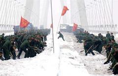 <p>Soldati spalano la neve sul ponte sul fiume Yangtze a Nanjing, nella provincia di Jiangsu, il 29 gennaio 2008. REUTERS/China Daily</p>