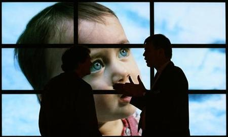 Two men chat in front of flat screens at an exhibition stand of the IFA 2007 consumer electronics fair in Berlin in this file photo from August 30, 2007. The mercury in a vaccine preservative is pumped out of a baby's body too quickly for it to do any damage, researchers reported on Wednesday in a study they say should further absolve shots of causing autism. REUTERS/Hannibal Hanschke