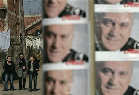 Serbs walk past election posters of hard line Serbian presidential candidate Tomislav Nikolic in the Kosovo town of Gracanica January 30, 2008. Kosovo will declare independence from Serbia with Western backing the weekend after the February 3 Serbian presidential election if nationalist Nikolic wins, political sources said on Wednesday. REUTERS/Hazir Reka