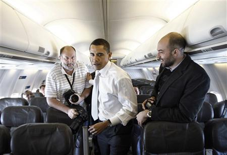 Democratic presidential candidate Barack Obama walks through the cabin on his chartered aircraft past photographers en route to Phoenix from Denver January 30, 2008. REUTERS/Jason Reed